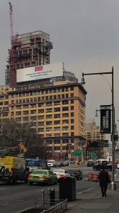 Here is an urban setting with a building and a NY lotto advertisement that claims to make New Yorkers rich.
