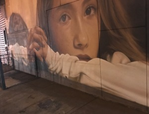 A street mural of a girl thinking.